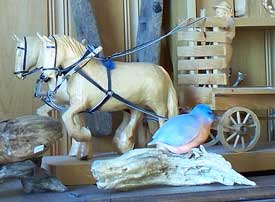 Carving of a horse pulling a wagon and of a bird on a piece of driftwood