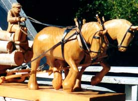 Carving of two horses pulling a wagon loaded with logs