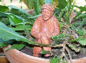 Garden decor - carving of tiny man placed in a potted plant